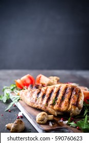 Grilled chicken breast on a wooden board with tomatoes and mushrooms on a concrete background with space for text