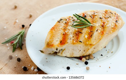 Grilled chicken breast with rosemary on white plate with wooden background - trendy rustic composition
