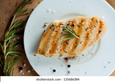 Grilled chicken breast with rosemary on white plate with wooden background - trendy rustic composition closeup from above