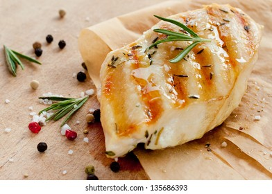 Grilled chicken breast with rosemary on wooden background - trendy rustic composition