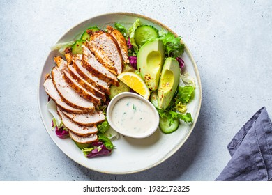 Grilled chicken breast salad with avocado, cucumber and mayonnaise dressing. Healthy food concept.