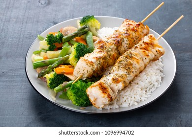 Grilled chicken breast skewers with steamed vegetables and long rice. Healthy eating concept