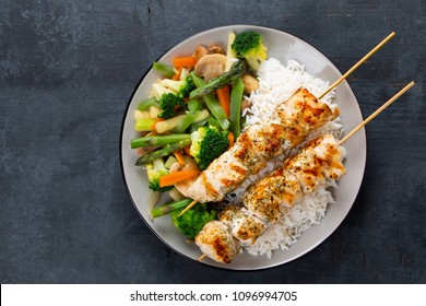 Grilled chicken breast skewers with steamed vegetables and long rice on a rustic blue wooden background. Top view
