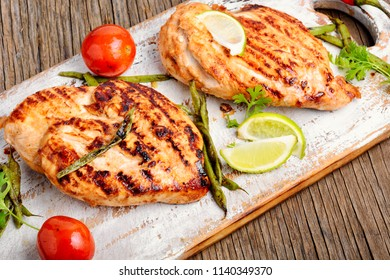 Grilled chicken breast with spices on kitchen board