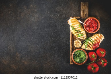 Grilled chicken breast with spicy sauces, tomatoes and herbs on dark rusty background copy space top view