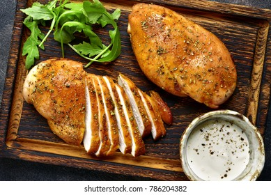 Grilled chicken breast in a sweet and sour marinade with yogurt sauce on a wooden cutting board.Top view.