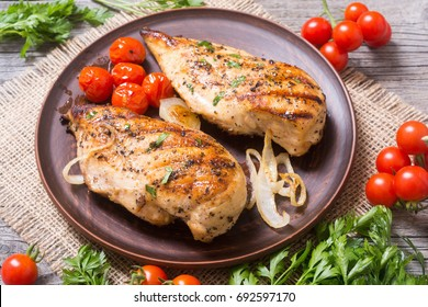 Grilled chicken breast with tomato , parsley and onion
