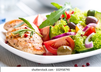 Grilled chicken breast with tomatoes, red pepper, organic green and kalamata olives, red onion, lettuce and fresh rocket and rosemary. Home made food. Concept for a tasty and healthy meal. Close up.