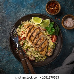 grilled chicken breast with vegetable couscous salad, top view, dark blue background, square image
