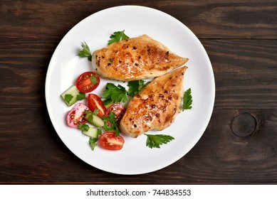 Grilled chicken breast and vegetable salad on wooden background, top view