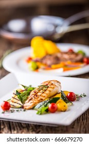 Grilled chicken breast with vegetables on oak table.