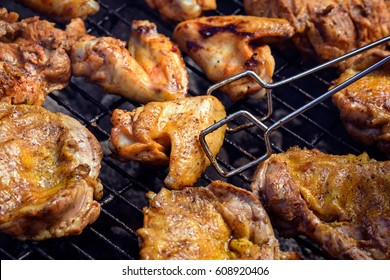 Grilled chicken breast, wings and legs. Barbecue chicken. Grilling meat with barbecue stuff. Grilled chicken on the flaming grill. BBQ.