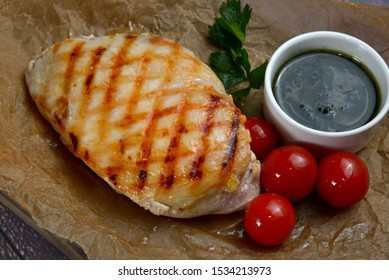 Grilled chicken breasts with ingredients on dark wooden table closeup view