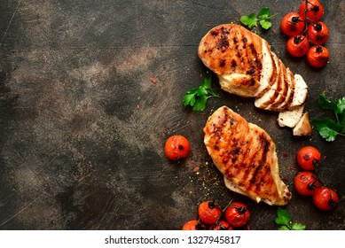 Grilled chicken breasts with roasted tomatoes on a dark slate, stone, metal or concrete background.Top view with copy space.
