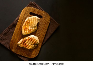 Grilled chicken breasts with spices on wooden desk. Top view. Space for copy