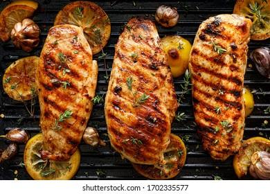 Poitrines de poulet grillées avec des tranches de thym, d'ail et de citron sur fond grill, vue de dessus