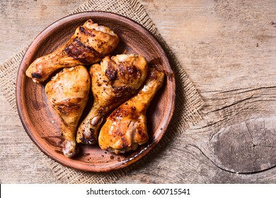 Grilled chicken drumsticks in pan .