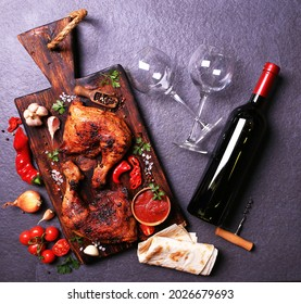 Grilled chicken drumsticks with spices and vegetables, with a bottle of red wine.
