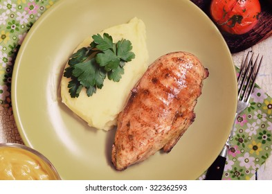 Grilled chicken fillet with mashed potatoes and grilled tomatoes. Rustic style.