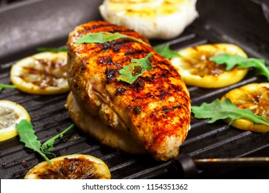 Grilled chicken fillet with spices and fresh vegetables in a pan on a black background
