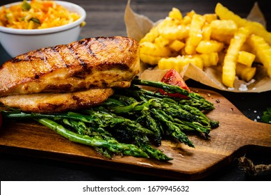 Grilled chicken fillet and vegetables on stone board