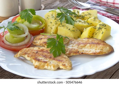 Grilled chicken fillets breasts and vegetables in plate