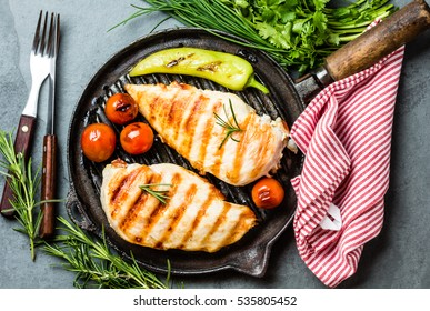Grilled chicken fillets, chili pepper and tomatoes cherry on grill iron pan, fresh herbs - rosemary and parsley, rustic cutlery on gray slate background. top view