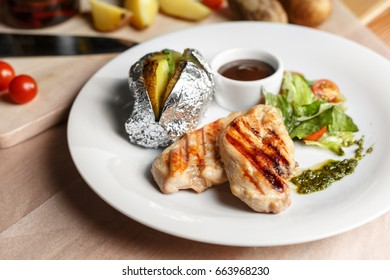 Grilled chicken fillets, chili pepper and tomatoes cherry. baked potatoes in foil