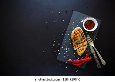 Grilled chicken fillets on slate plate with rosemary, pepper, ketchup and spices on dark wooden background. Top view. Flat lay. Copy space