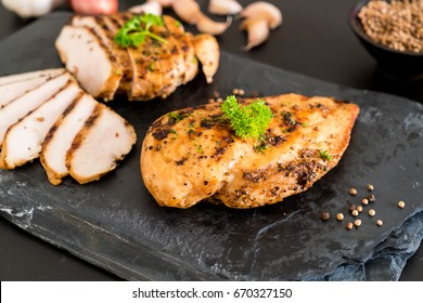 Grilled chicken fillets on slate plate