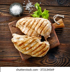 grilled chicken fillets on wooden cutting board, top view