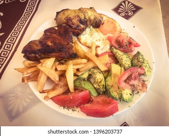 Grilled chicken with fried egg, french fries, tomato and avocado