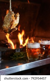 Grilled chicken hanged in front of burning flames and cold beer