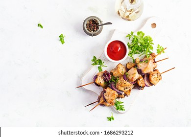 Grilled chicken kebab with red onions on a light table. Grilled meat skewers, shish kebab on light background. Top view, overhead, flat lay
