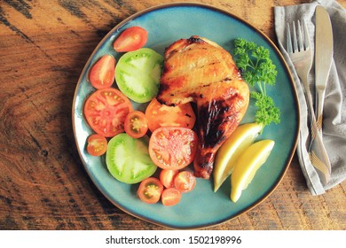 Grilled chicken leg quarters with crispy golden brown skin, tomatoe ,lemon on dark wooden boards. Food background. Top view