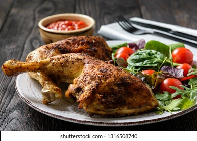 Grilled chicken leg quorters with salad mix and tomatoes.