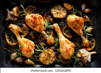 Grilled chicken. Grilled chicken legs, drumsticks with addition  garlic, lemon and rosemary on grill plate, top view. Grill food