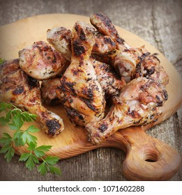 Grilled chicken legs on cutting board.Rustic dinner background