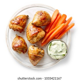grilled chicken legs on wooden cutting board isolated on white background, top view