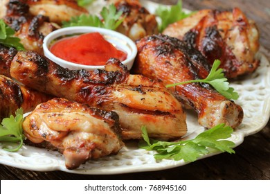 Grilled chicken legs on wooden table served on white plate with coriander