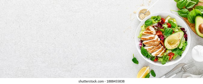Grilled chicken meat and fresh vegetable salad of tomato, avocado, lettuce and spinach. Healthy and detox food concept. Ketogenic diet. Buddha bowl dish on white background, top view. Banner. - Shutterstock ID 1888455838