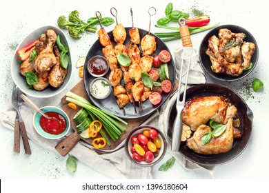 Grilled chicken meat meals on table. Assortment of tasty bbq snack with fresh vegetables. Top view