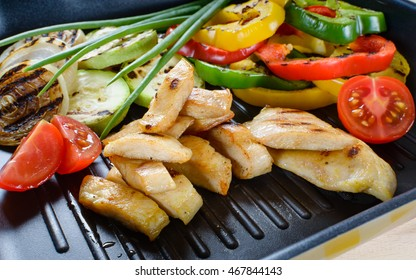 Grilled chicken meat on grill with vegetables in the background.