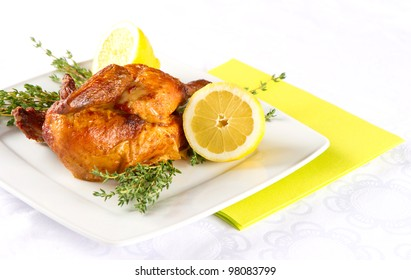 grilled chicken on a white plate with herbs and lemon