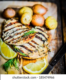 Grilled chicken with potatoes and herbs on wooden background
