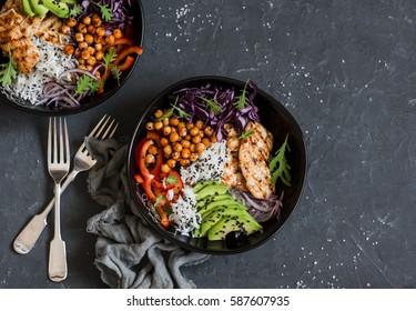 烤鸡肉,米饭,辣鹰嘴豆,鳄梨,白菜,胡椒佛碗在深色背景,顶视图。 美味均衡的食物概念