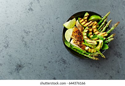 Grilled Chicken Salad with Grilled Asparagus and Avocado. Paleo diet. Healthy nutrition. Concept for a tasty and healthy meal. Top view. Flatlay. Copy space.