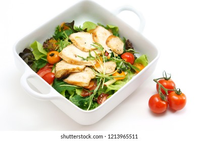 Grilled chicken salad with lettuce and tomato on white background.