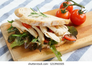 Grilled chicken sandwich with lettuce and tomato on wooden plate.
