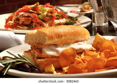 Grilled chicken sandwich with melted provolone and sweet potato chips served at an outdoor restaurant